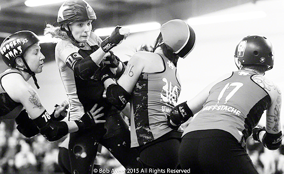 Ethel Vermin scored 68 points for the Throttle Rockets in their bout last Saturday night against Grave Danger. Hard earned here as she struggles to get past Danger pivot StunHer and blockers Rodger That and Muffstache. Photo by Bob Ayers.