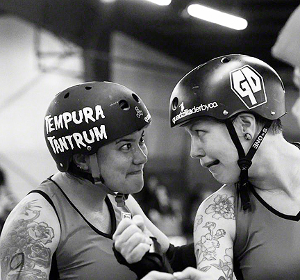 Grave Danger skaters Tempura Tantrum and Muffstache reflect each   other's intensity early in their bout against Derby Liberation Front.   Photo by Bob Ayers.